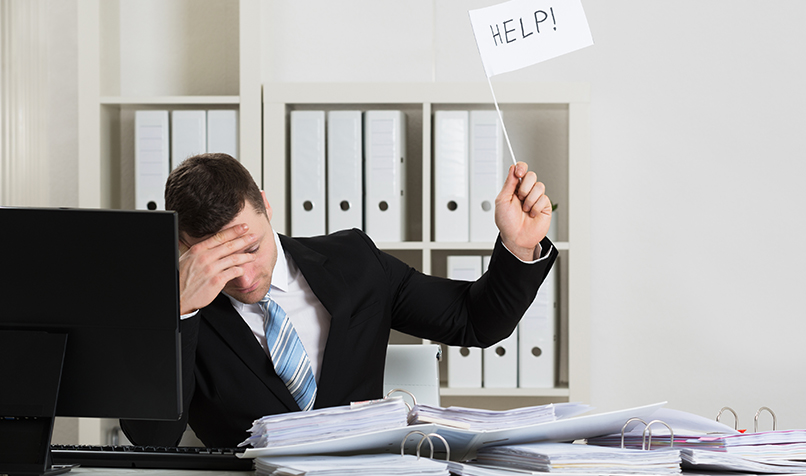 man holding up white flag with help on it at his desk in a boardroom with an opn lapto and his head in his hands sad face for leadership mistakes blog