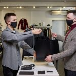 two males wearing black mask each one passing a black bag to the other for for customer service training healthy business builder