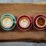 five different cups of coffee lined up on a wooden board in colourful mugs