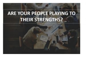 photograph of business workers sitting around a table with above title over transparent image asking, ARE YOUR PEOPLE PLAYING TO THEIR STRENGTHS?