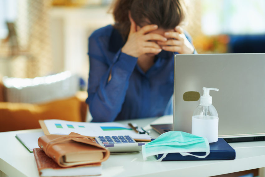 lady with head in hands at laptop and desk suffering from moral fatigue
