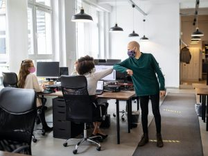 office workers wearing masks elbow bumping at desk on their return to work