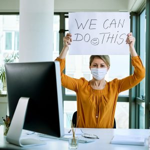 """office lady with mask on and a sign """"we can do this"""" return to work"""
